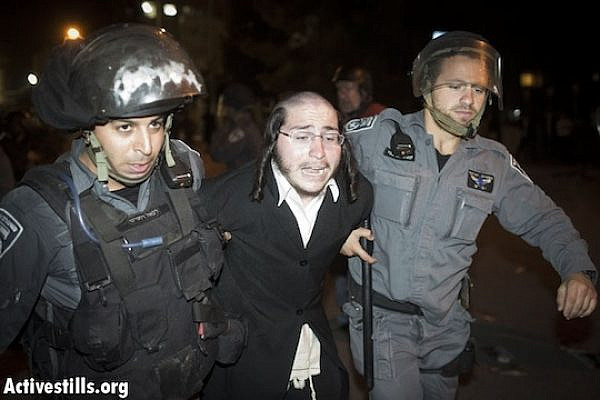 Police arrest an ultra-Orthodox man at a mass demonstration against plans to draft haredim into the Israeli army. (Oren Ziv/Activestills.org)
