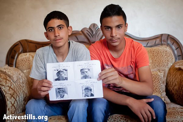 "Two Palestinian boys age 14 and 15 hold a poster with their own photos on it with Arabic writing that reads: ""We are the army. Be careful, we will arrest you if we see you, or come to your home."" The poster was posted on the village walls and near one of the boy's houses by Israeli soldiers during an army raid on the village on the night of May 31, 2013. (Photo by: Shiraz Grinbaum/Activestills.org)"