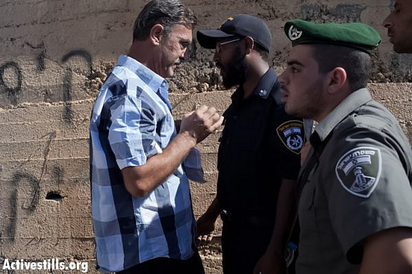 "A Palestinian man stands in front of Israeli border policemen next to an outer wall of his house that had a graffiti writing sprayed on it, reading: ""We will not remain silent over stone throwing"" (loose translation). The price tag action in which two Palestinian-owned houses were spray painted and at least 20 cars were vandalized took place in the Palestinian neighborhood of Beit Hanina in East Jerusalem, June 24, 2013. (Photo by guest photographer: Tali Mayer/Activestills.org)"