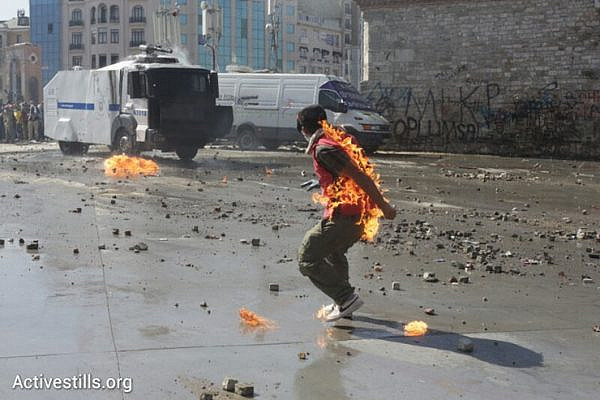 A demonstrator burning from a molotov intended to be thrown toward the police during Turkey's riot police raid on Taksim Square, Istanbul, June 11, 2013. Photo by: Oren Ziv/Activestills.org