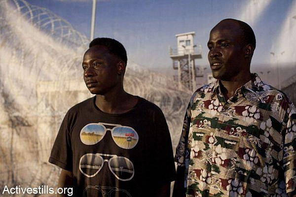 Refugees pose infront of a poster of Saharonim prison, during the Refugee Day in tel Aviv on June 20, 2013. (Keren Manor/Activestills.org)