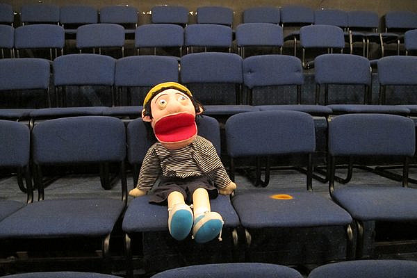 A puppet fills one seat in the empty El-Hakawati Theater on June 27, 2013 in East Jerusalem. The theater would have been filled with children and families, but the Israeli Public Security Ministry canceled the annual festival. (photo: Matt Surrusco, +972 Magazine)