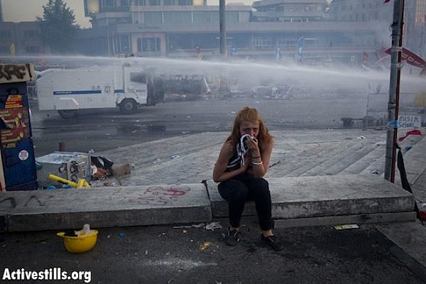 A woman reacts to tear gas, as police evict Taksim Square for the second time on Tuesday. June 11, 2013. (Oren Ziv/Activestills.org)