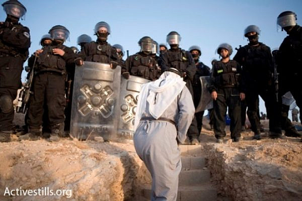A Bedouin man confronts Israeli policemen during the destruction of the unrecognized village of Al-Araqib (photo: Activestills)
