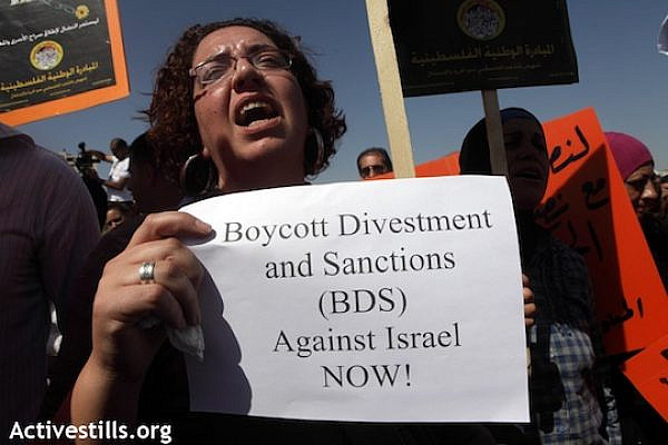 A woman carries a sign in support of the Boycott, Divestment and Sanctions (BDS) campaign, October 11, 2011 (Anne Paq/Activestills.org)
