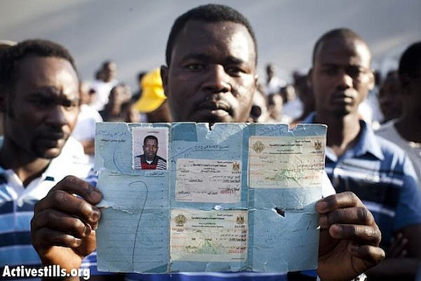 Ibrahim, a refugee from Sudan, holds a document given to him by the UN in Egypt, as he takes part in a protest held by refugees and activists outside the UN offices in Tel Aviv, June 10, 2012 (Oren Ziv/Activestills.org)