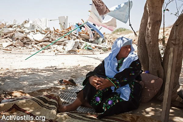 "Sanda Abulkian sits outside her demolished house in the ""unrecognized"" village of Atir on July 12, 2013. Abulkian house was demolished four times already, three of them during 2013. The family has since received a demolition order for the tent in which they live now. (Photo by: Keren Manor/Activestills.org)"