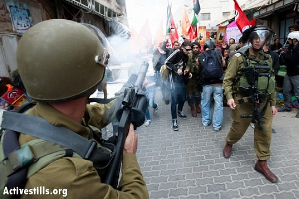 An Israeli soldier fires tear gas toward Palestinian, Israeli, and international activists during a demonstration against the occupation and in support of Palestinian prisoners the West Bank city of Hebron, March 1, 2013. (Photo by: Ryan Rodrick Beiler/Activestills.org)