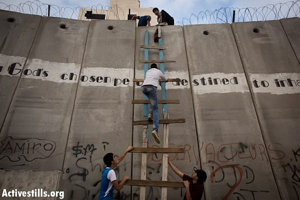 Palestinians use a ladder to climb over the Israeli wall in A-Ram, north of Jerusalem, on their way to Al-Aqsa mosque, in the Old city of Jerusalem to attend the second Friday prayer in the fasting month of Ramadan, 19 July 2013. (Photo by: Oren Ziv/ Activestills.org)