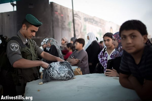 A Israeli border policeman check the bag of a Palestinian woman as she waits to cross Qalandiya checkpoint outside Ramallah, West Bank, into Jerusalem to attend the second Friday Ramadan prayers in the Al-Aqsa Mosque, July 26, 2013. (Photo by: Oren Ziv/ Activestills.org)