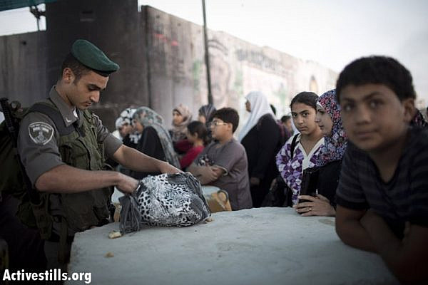 A Israeli border policeman check the bag of a Palestinian woman as she wait to cross from Qalandiya checkpoint outside Ramallah, West Bank, into Jerusalem to attend the Ramadan Friday Prayer in the Al-Aqsa Mosque, July 26, 2013. Photo by: Oren Ziv/Activestills.org