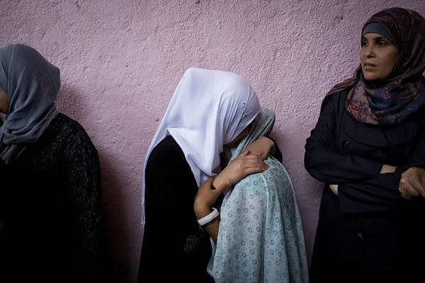 Relatives of of Jihad Aslan mourn during his funeral at Qalandiya Refugee Camp near the West Bank city of Ramallah, August 26, 2013. In the early hours of August 26, an undercover unit of the Israeli border police entered the refugee camp and tried to arrest a wanted Palestinian man, but the force was discovered by the residents, who clashed with the soldiers. During the clashes, three Palestinians were shot to death: Yunis Jahjouh, 22, Rubeen Abed Fares, 30, and Jihad Aslan, 20. According to Palestinian medics, 19 others were injured. (photo: Oren Ziv/Activestills.org)