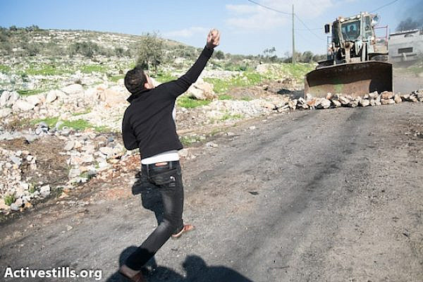 A Palestinian youth throws stones at an Israeli army bulldozer in Kufr Qaddum, December 28, 2012 (Yotam Ronen/Activestills.org)