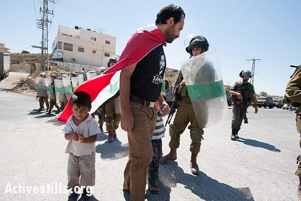 Palestinian activist Mohammad Brijiah and his twin 3-year-old sons confront Israeli forces blocking the road from their West Bank village of Al Ma'sara during a weekly demonstration against the separation barrier, September 6, 2013. If built as planned, the wall would cut off the village from its agricultural lands.