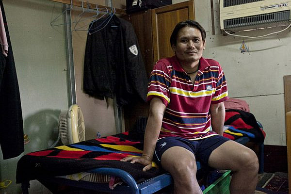 A worker in his room, Kfar Varburg, August 31, 2013. (Shiraz Grinbaum/Activestills.org)