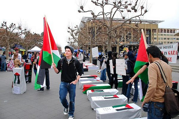 SJP member holds Palestinian flag in front of make-shift coffins at Sproul Plaza on Jan. 21, 2009.  SJP was protesting the Israeli attacks on Gaza, Palestine which took place on December 2008 through January 2009. (photo: Ramsey Al-qare)