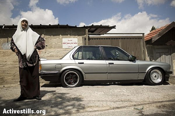 A Palestinian woman stands next to a car that had its tires slashed in Sheikh Jarrah in East Jerusalem, September 22, 2013 (Activestills.org)