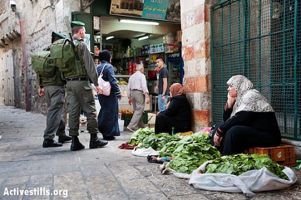 Israeli border police patrol near Palestinian women selling vegetables in the Old City near Damascus Gate, East Jerusalem, May 19, 2013. (Ryan Rodrick Beiler/Activestills.org)