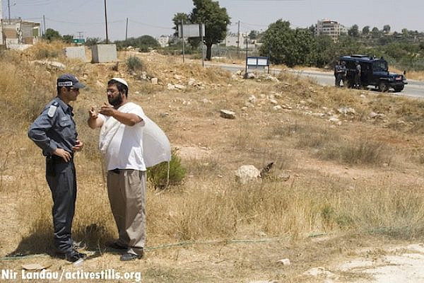 A settler speaks with an Israeli police officer in the West Bank (Photo: Activestills.org)