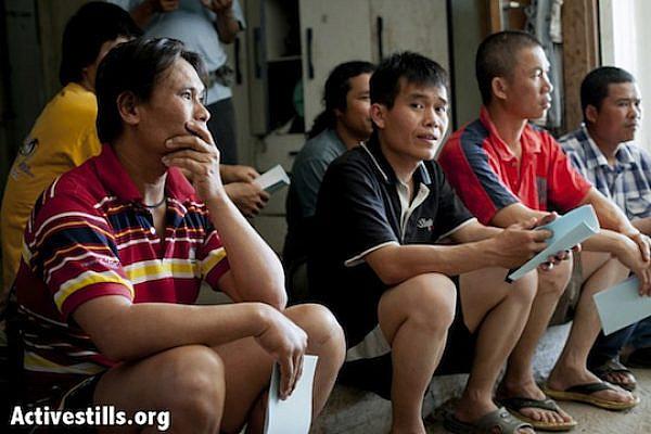 Thai workers sitting and listening at their residence in Kfar Varborg. (Shiraz Grinbaum/Activestills.org)