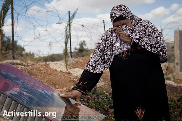 Subhiyeh Abu Rahmeh cries near the memorial monument for her son, Bassem, who in a 2009 protest was shot and killed with a high-velocity tear gas canister fired by an Israeli soldier, Bil'in, West Bank, October 4, 2013. (Oren Ziv/Activestills.org)