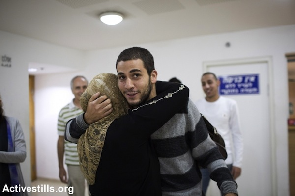 Palestinian Activist Razi Nabulsi hugs his mothers following his release from jail, in Haifa court, October 16, 2013. (Photo: Oren Ziv/Activestills.org)