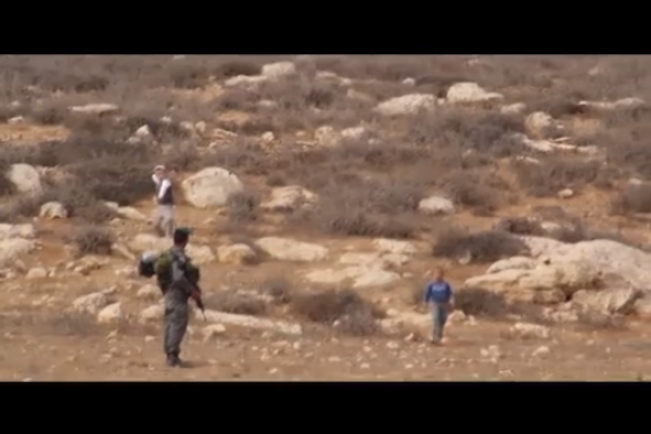 A Border Policeman looks on as a six-year-old Palestinian and a settler child share a moving moment. Almost. (screenshot: YouTube)