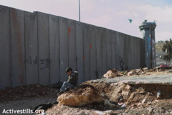 A Palestinian child sitting in front of a section of the Separation Wall in the refugee camp of Shuafat, East Jerusalem, December 27, 2011. (Photo: Anne Paq/Activestills.org)