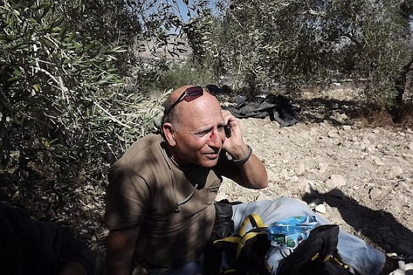 A man's face is bloodied after being attacked by Jewish extremists who descended from the direction of Yitzhar toward Palestinians and Israeli volunteers picking olives in Burin, October 20, 2013. (Photo: Munir Qadus / Yesh Din)