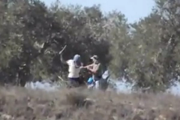 A mask settler strikes a Palestinian olive picker with a metal pole near the West Bank village of Burin. (Screenshot: Monir Kados/Yesh Din)