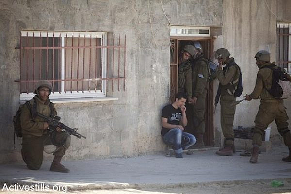 Illustrative photo of Israeli soldiers raiding a Palestinian home and making an arrest in 2012 (Oren Ziv/Activestills.org)