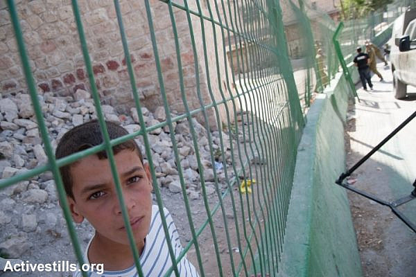 A Palestinian child watches as Israeli soldiers place a concrete and steel barrier to segregate Palestinian pedestrians from Israeli traffic along a road in the H2 section of Hebron, October 22, 2013. The road connects the Ibrahimi Mosque (Tomb of the Patriarchs) in Hebron's old city with the nearby Israeli settlement Kiryat Arba. Israelis are allowed to drive on the road, but Palestinians are prohibited from driving there without special permission. All settlements in the occupied Paletinian territories are illegal under international law. (photo: Ryan Rodrick Beiler/Activestills.org)