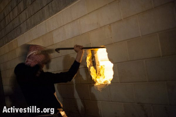 Palestinian activists break a hole in the Israeli separation wall dividing land belonging to the West Bank town of Al Khader in the late night hours of November 22, 2013. (photo: Activestills)