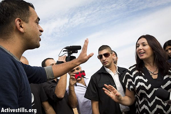 A Bedouin activist argues with MK Miri Regev, during a tour by the Israeli Knesset Internal Affairs Committee in the Negev, regarding the Prawer Plan, in the Bedouin city of Rahat, Novmber 24, 2013.