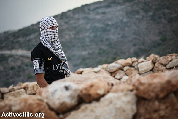 A Palestinian youth during the weekly protest against the Wall in the West Bank village of Bil'in, November 1, 2013. One Palestinian youth was shot in the leg with live ammunition during the demonstration and evacuated to Ramallah hospital.  (Photo by: Hamde Abu Rahma/ Actviestills.org)