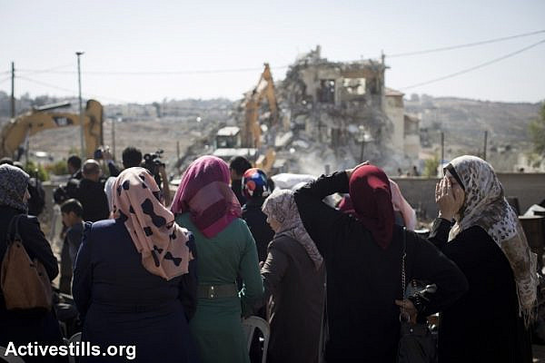 Palestinian women look on and react as Jerusalem municipality workers demolish a residential building in an East Jerusalem neighborhood of Beit Hanina, on October 29, 2013. (Oren Ziv/Activestills.org)