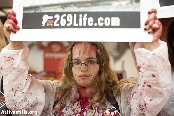 #269Life animal rights activists protest in a supermarket owned by the meat company Soglowek in the northern Israeli city of Nahariya, spraying red paint on the counters, November 20, 2013. Eleven activists were arrested. (Photo: Activestills.org)