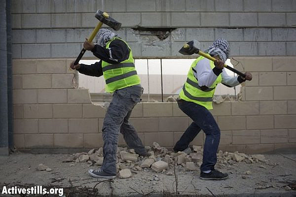 Palestinians use hammers to break through the separation wall in the West Bank village of Bir Nabala. (photo: Activestills)