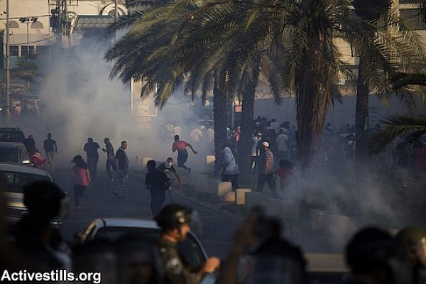 Israeli police fire tear gas toward and forcefully disperse demonstrators during a protest against the Israeli government's Prawer-Begin Plan, on road 65 near the northern town of Ar'ara. (Photo: Activestills.org)