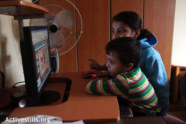 Palestinian children in Gaza use a computer. (Illustrative photo: Anne Paq/Activestills.org)