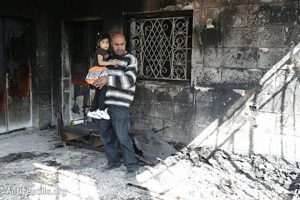 Khaled Abed a-Rahman Dar Khalil surveys the damage to his home while holding his daughter. Seven members of the Khalil family were inside their home when it was firebombed by Israeli extremists early Thursday morning. (Photo: Oren Ziv/Activestills.org_