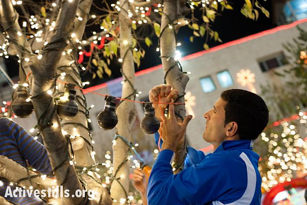 A Bethlehem-area activist hangs U.S.-made tear gas grenades used by the Israeli military in nearby Aida Refugee Camp on trees decorated for Christmas in Bethlehem's Manger Square, West Bank, December 2, 2013. (photo: Ryan Rodrick Beiler/Activestills.org)