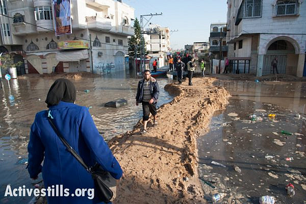 Palestinians pass along a sand walkway connecting flooded areas of the Al Nafaq neighborhood of Gaza City. (photo: Ryan Rodrick Beiler/Activestills.org)
