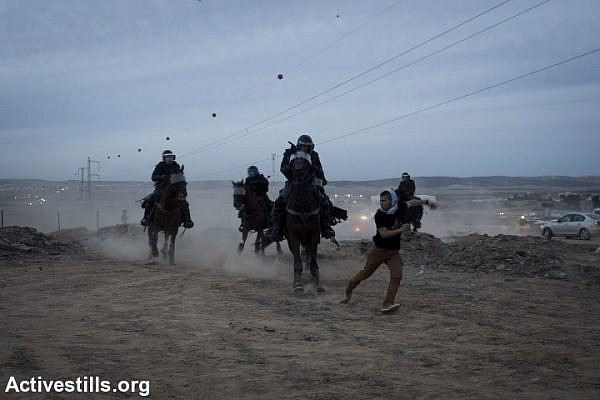 Mounted Israeli policemen chase a Bedouin youth during a protest against the Israeli government's Prawer Plan, on road 31 on November 30, 2013 near the town of Hura, Israel.