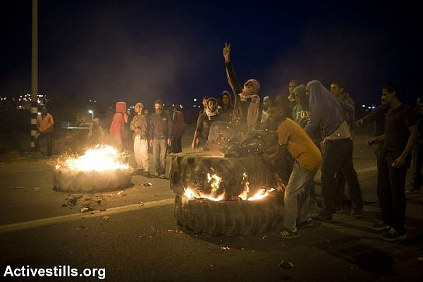 Bedouin youth set tires barricade on fire during a protest against the Israeli government's Prawer Plan, on road 31 on November 30, 2013 near the town of Hura, Israel.