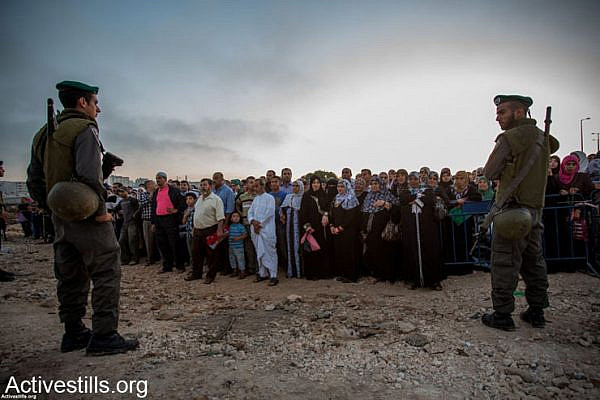 Border police officers stands in front of Palestinians as they wait to cross from Qalandiya checkpoint outside Ramallah, West Bank, into Jerusalem to attend the Ramadan Friday Prayers in the Al-Aqsa Mosque, July 26, 2013.