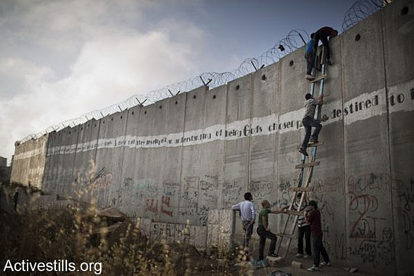 Palestinians use a ladder to climb over the Israeli wall in A-Ram, north of Jerusalem, on their way to Al-Aqsa mosque, in the Old city of Jerusalem to attend the second Friday prayer in the fasting month of Ramadan, 19 July 2013.