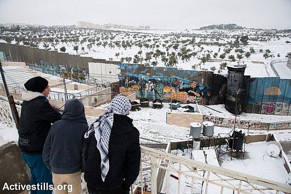 Palestinian youth stand on a rooftop in Aida Refugee Camp overlooking the Israeli separation wall and snow-covered olive groves on the other side, Bethlehem, West Bank, December 14, 2013. (photo: Activestills)
