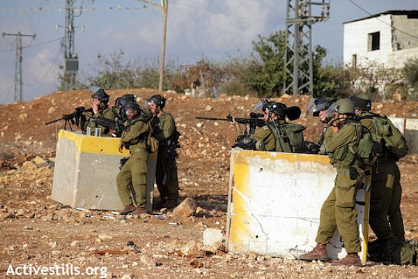 Illustrative photo of an Israeli soldier aiming his weapon at Palestinian protesters. (Photo: Anne Paq/Activestills.org)