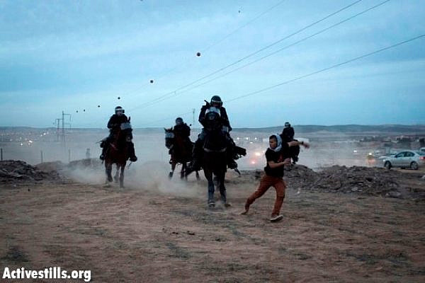 Mounted riot police chasing a demonstrator in the Negev Day of Rage, Hura, November 30, 2013 (Oren Ziv/Activestills.org)